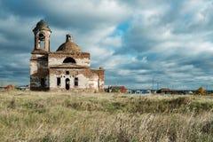 Iglesia destruida en el medio de un campo sobre el cielo con las nubes de funcionamiento y la hierba seca abajo imagen de archivo