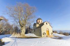 Iglesia en la colina de la nieve de la montaña Foto de archivo