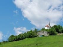 Iglesia en la colina, el bosque y el cielo azul con las nubes blancas fotos de archivo