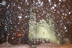 Iglesia en la noche con nieve que cae Imagen de archivo