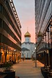 Iglesia entre los edificios de oficinas de cristal en la puesta del sol imagen de archivo