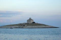 Iglesia-faro en la pequeña isla Fotos de archivo