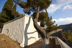 Iglesia griega tradicional con el árbol de pino crete Grecia Imagenes de archivo
