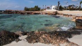 Iglesia griega tradicional en la playa hermosa de Nissi cerca de Ayia Napa en la isla de Chipre metrajes