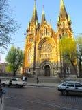 Iglesia hermosa, vieja en el estilo gótico, cerca de la calle de la ciudad foto de archivo