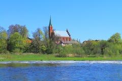 Iglesia luterana de Lazdenen de 1578 de la construcción en la orilla del río a Sheshupa Imágenes de archivo libres de regalías