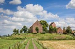 Iglesia medieval en un montón en el pueblo Ezinge de Groninga Imágenes de archivo libres de regalías