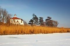 Iglesia ortodoxa cerca de un lago congelado en la puesta del sol Foto de archivo