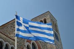 Iglesia ortodoxa de Konstantinos With The Beautiful Blue y de la bandera griega blanca que agitan en el viento Viaje de la histor fotografía de archivo libre de regalías