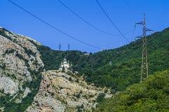 Iglesia ortodoxa en las montañas y la línea eléctrica Foto de archivo