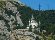 Iglesia ortodoxa en las montañas y la línea eléctrica Foto de archivo libre de regalías