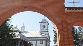 Iglesia ortodoxa, la puerta de la entrada al territorio de la iglesia ortodoxa, el arco, día soleado, árboles verdes almacen de video