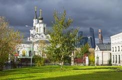 Iglesia ortodoxa y el centro de negocios moderno contra el gris Fotos de archivo