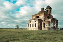 Iglesia quebrada arruinada vieja en el fondo del cielo y de un campo seco, nubes borrosas imagenes de archivo