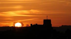 Iglesia silueteada contra una puesta del sol de oro Foto de archivo