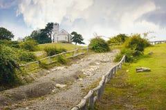 Iglesia solitaria en la cima de una colina de la montaña Prado verde con el tre fotografía de archivo libre de regalías