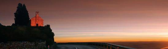 Iglesia vieja solitaria de la montaña en puesta del sol Panorama Fotos de archivo