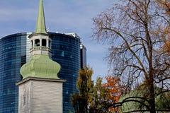 Iglesia vieja y un centro de ciudad moderno Imágenes de archivo libres de regalías