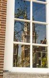 Iglicy stary kościół odbijają w okno w Amsterdam, holandie obrazy stock