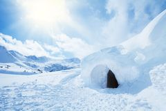 Igloo and high snowdrift. Igloo and snow shelter in high snowdrift with mountains peaks on background Stock Image