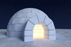 Igloo icehouse with warm light inside under night sky with stars Royalty Free Stock Photo