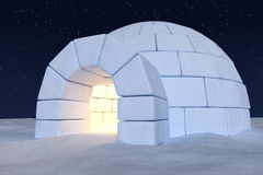 Igloo icehouse with warm light inside under night sky with stars Stock Image