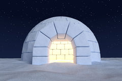 Igloo icehouse with warm light inside under sky with night stars Stock Photos