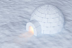 Igloo icehouse with warm light on snow aerial view. Eskimo house igloo icehouse with warm light inside made with snow at night on the surface of snow field Stock Photo