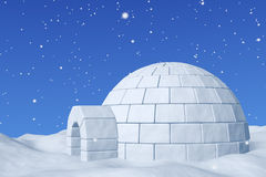 Igloo snowhouse under blue sky with snowfall closeup. Winter north polar snowy landscape - eskimo house igloo snowhouse made with white snow on the surface of Stock Photos