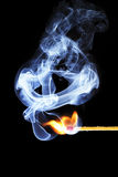 Ignite 2. One match is igniting in front of black background with blue smoke stock photos