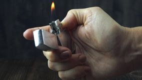 Ignite a lighter in the hand on dark background. Close up stock video