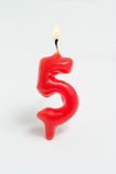 Ignited candle number five Royalty Free Stock Image