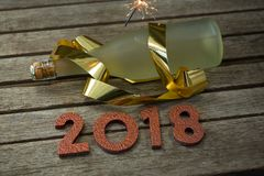 Ignited sparkler, bottle of champagne and year 2018. On a wooden surface Stock Images