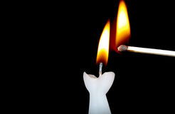 Igniting candle. With a match royalty free stock image