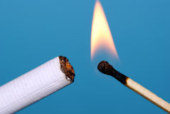 Ignition cigarettes. Burnt cigarette flame on a blue background Stock Photography