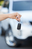 Ignition key hanging in female hand with defocused car Royalty Free Stock Photo