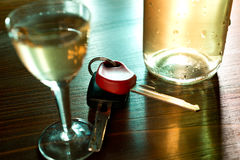 Ignition key and hard liquer. Car key nand glass of liquer on the table Stock Photo