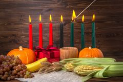 Ignition of Kwanzaa traditional candles, festival concept with g. Ift box, pumpkins, ears of wheat, grapes, corns, banana, bowl and fruits on wooden background Royalty Free Stock Photo