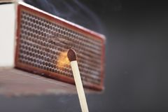 Ignition of a match. A Match ignited by rubbing the match head against a match box Stock Photo