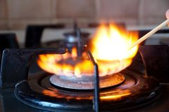 Ignition of a gas ring on the stove. Ignition by a match of a gas ring on the stove Royalty Free Stock Photo
