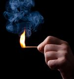 Ignition of match with smoke. Iignition of match with smoke at black background Royalty Free Stock Images