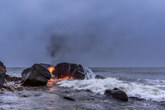 Ignition sea water. Flame between of the boulders on the seashore Stock Photos