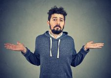 Portrait of a young man shrugging shoulders feeling clueless. Ignorance and arrogance. Portrait of a young man shrugging shoulders feeling clueless isolated on royalty free stock photo