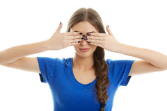 Ignorance. Young serious woman in blue T-shirt covering her eyes with her hands over white background Royalty Free Stock Photography