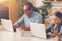 Ignorando o pai e a filha que trabalham em portáteis em casa Imagem de Stock