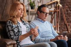 Ignorant couple using cellphones at home. Ruined private life. Involved mature captured couple sitting on the couch at home and using mobiles while surfing the Stock Photo