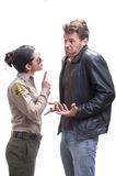 Ignorant suspect. Petite young female Hispanic sheriff deputy questions and warns tall male Caucasian suspect on white background Stock Photo