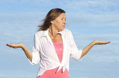 Ignorant, unaware woman gesturing isolated. Mature woman shrugging innocent and confused shoulders, gesturing with arms up, isolated with blue sky as background Royalty Free Stock Images