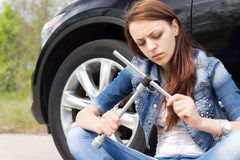 Ignorant woman frowning at a wheel spanner Royalty Free Stock Photos