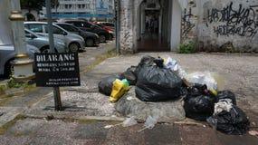 Ignorer l'avertissement d'enseigne Le plastique prient et des déchets sur le bord de la route images stock